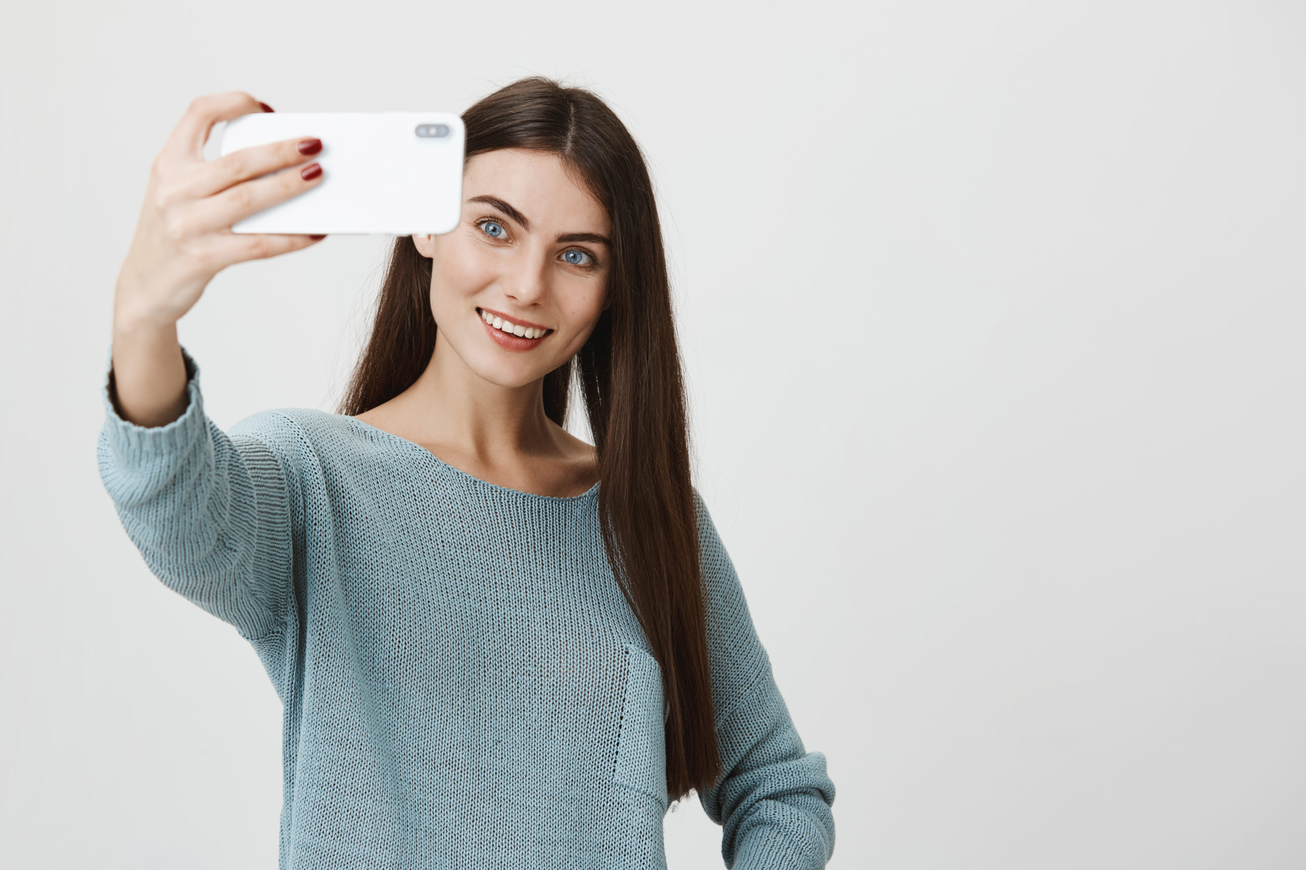 Beautiful caucasian young female with dark long straight hair, appealing blue eyes in casual clothes holding mobile phone, posing for selfie. Smiling pretty girl making video call.